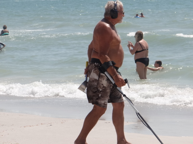 Summer beach detectorists actually just checking out chicks.